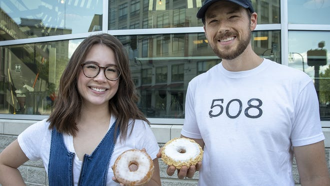 Susan and Joseph Skrzek are opening Glazy Susan in the DCU Center soon. They are photographed with their namesake glazy susan donut, left, and their guava cheesecake donut.