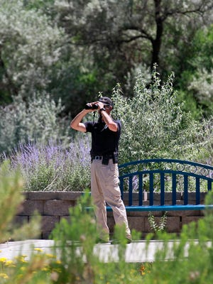Ron Paquin, a school resource officer with the Farmington Police Department, searches on Friday along the Animas River near the Farmington Museum at Gateway Park for a man suspected of trying to run over an officer with a vehicle.