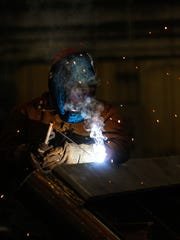 Lorenzo Yazzie a welder with Mining Equipment Inc. works on Nov. 3 in the company's fabrication shop at their manufacturing center in Farmington.