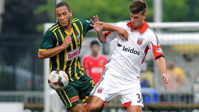 Rochester's Tony Walls, left, fights off a challenge for the ball by D.C. United's Conor Doyle in a U.S. Open Cup fourth-round game on January 17, 2014.