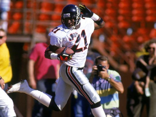 Deion Sanders struts to the end zone after intercepting a pass.