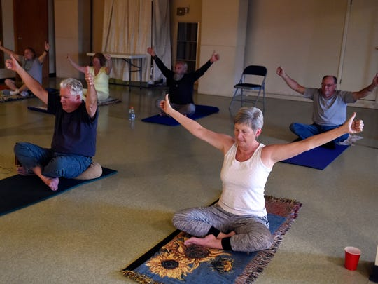 """Participants take part in a yoga class at the Zion Center for Spiritual Development and Healing in Evansville recently.  The longtime director of the United Caring Shelter has opened a spiritual healing center near the shelter where people can """"pay what they can"""" for vegan meals, yoga classes and other """"healing practices."""""""