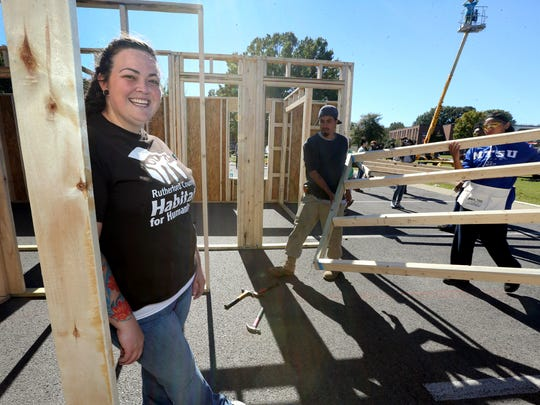 Soon-to-be home owner Nikki Newbold stands next to her under-construction home.
