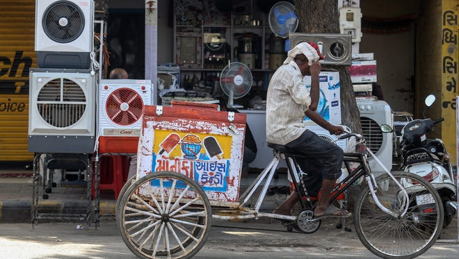 An ice cream vendor rides past a shop selling air conditioners and fans, in Ahmedabad, India, on May 28, 2015.