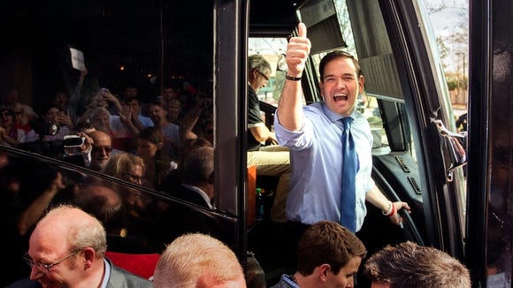 Marco Rubio gives a thumbs-up to supporters as he boards