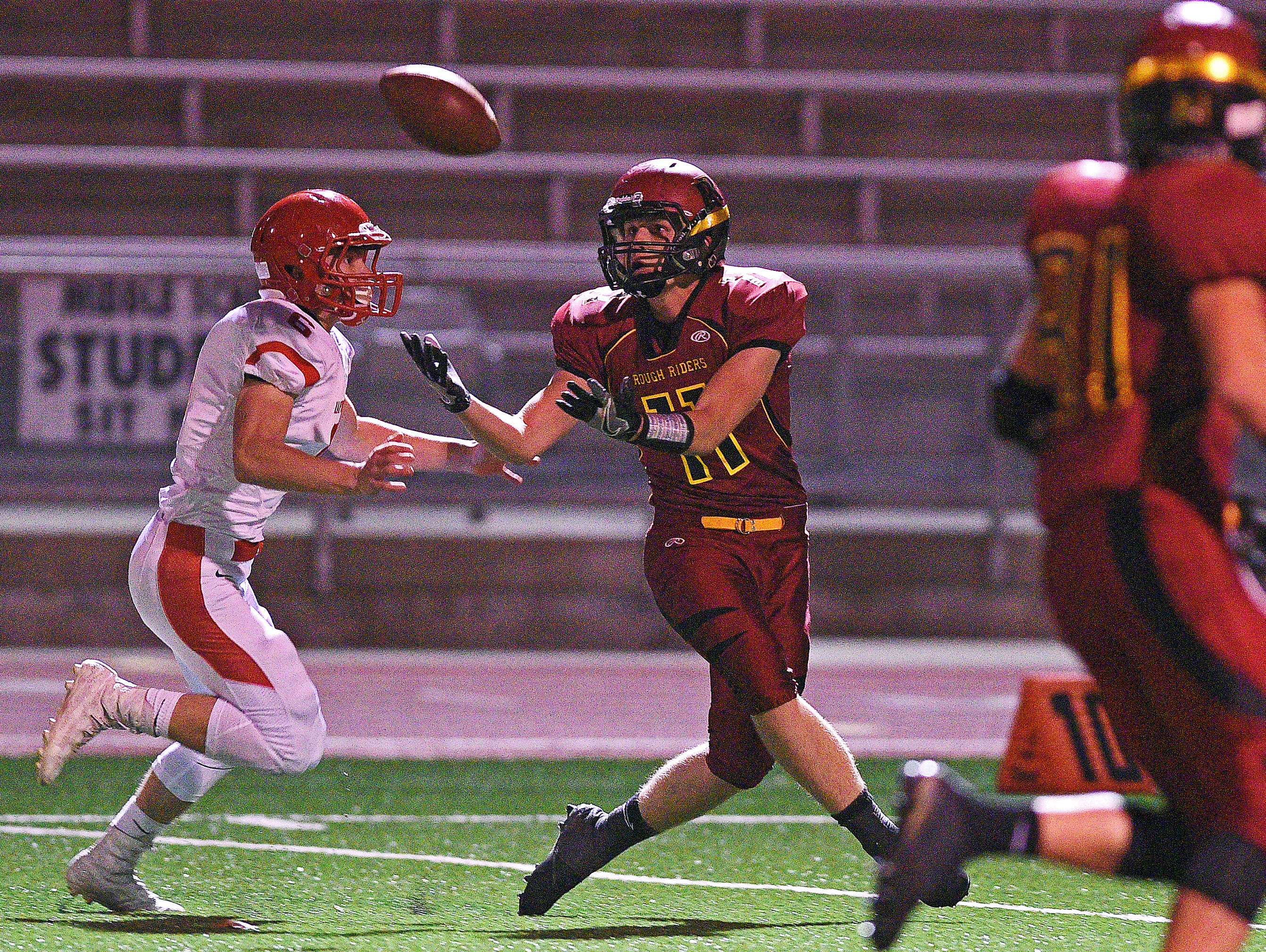 Roosevelt's Austin Johnson (11) catches a pass in front of Rapid City Central's Tate Remmers (6) during a game Friday, Oct. 14, 2016, at Howard Wood Field in Sioux Falls.