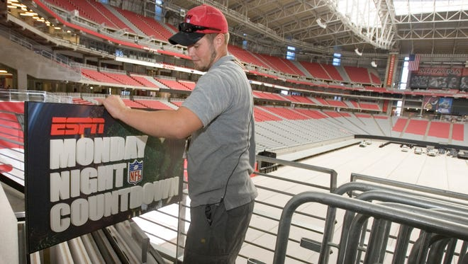 Grant Wisuri checks a sign for ESPN's Monday Night Football prior to a 2006 game in Glendale.