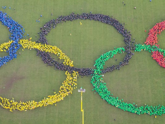 An aerial view shows thousands of  people wearing colorful ponchos  as they form the Olympic rings to support Hamburg's bid for the Olympics 2024,  in a park in Hamburg, Germany, Sunday Nov. 8,  2015.  (Daniel Bockwoldt/dpa via AP)