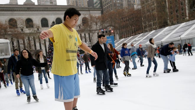 Ian Chan, 15, wears shorts and a T-shirt while ice skating at Bryant Park in New York on Dec. 23, 2015.
