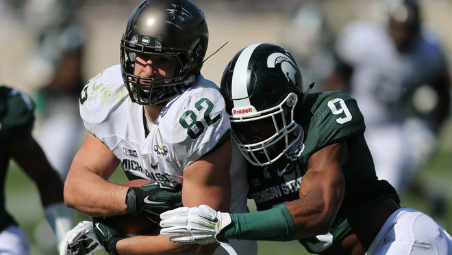 Michigan State tight end Josiah Price is tackled by the Montae Nicholson during Saturday's spring game in East Lansing.