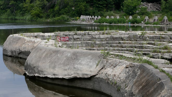 A small pocket of contaminated muck in front of this serpentine concrete and stone wall in the Milwaukee River will be dredged next year, as part of the demolition of the Estabrook Park dam. The deteriorated wall and dam will be removed by the Milwaukee Metropolitan Sewerage District.