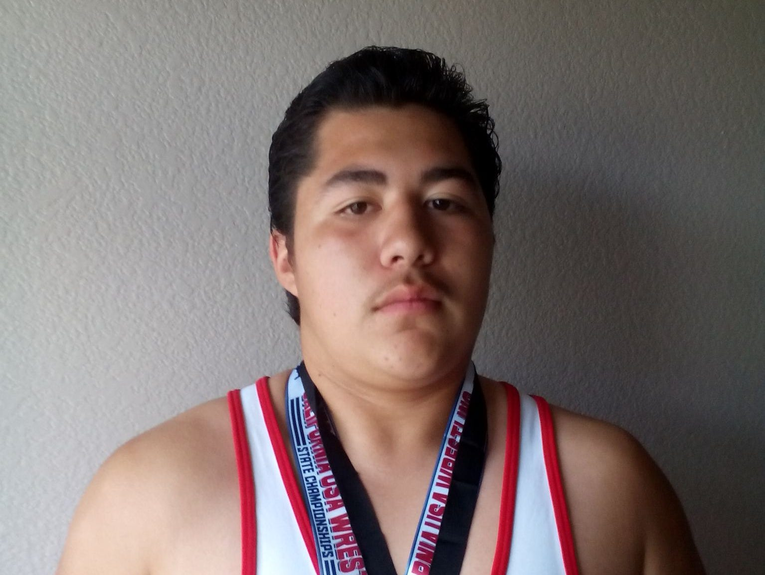 Zachary Ruelas poses with some of his medals he's earned in wrestling over the years