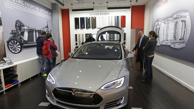 Customers check out a Tesla car in Cincinnati. The automaker has applied for dealership and repair facility licenses in Michigan.
