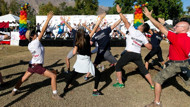 Participants stretch before the start of the 2014 Desert AIDS Walk at Ruth Hardy Park in Palm Springs.