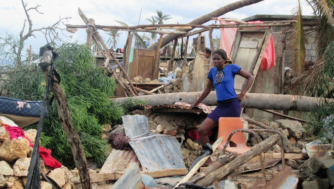 This handout photo obtained from the Agency for Technical Cooperation and Development Assistance (ACTED) on Oct. 7, 2016 shows a woman looking on in the devasted town of Jeremie, west Haiti, following Hurricane Matthew.  Hurricane Matthew.