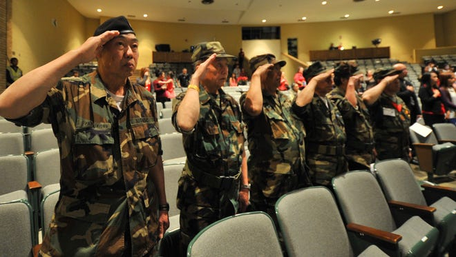 Hmong veterans salute during the national anthem to open the ceremony of the fourth annual Qhuas Peb Lub Npe Hmoob Zoo event Saturday at D.C. Everest High School Auditorium in Weston.