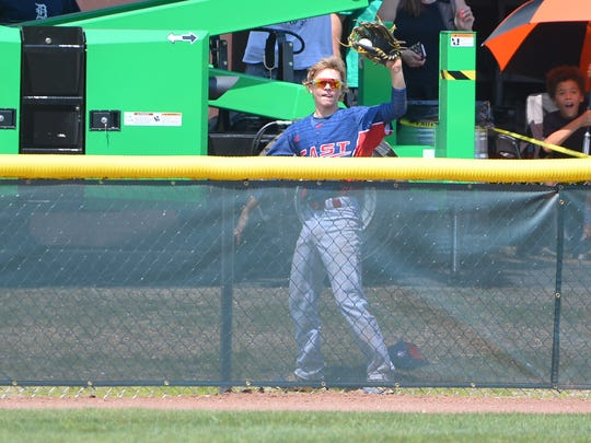 Jack Regenye gets up off the ground and shows the umpire the ball after making the over-the-fence catch.
