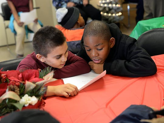 """Adian Sierra, 10, and A'zhone Burden, 8, both of Bridgeton (from left), sing """"Silent Night"""" with other children at the NIA Amity Heights Apartments Christmas party, Wednesday, Dec. 16 in Bridgeton."""