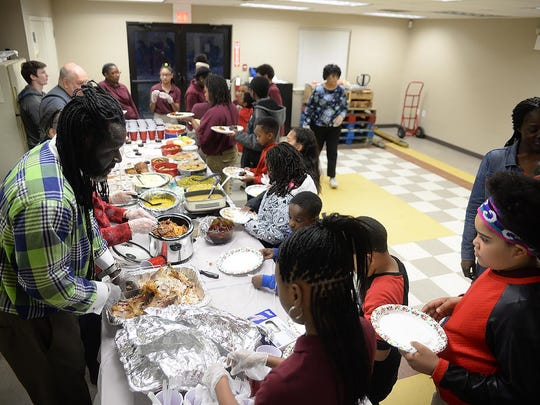 Minister Keith Howard (left) of Wings of Love Ministry, serves a traditional Christmas dinner to children, including Dali Rivera, 9, of Bridgeton, at the NIA Amity Heights Apartments Christmas party, Wednesday, Dec. 16 in Bridgeton.