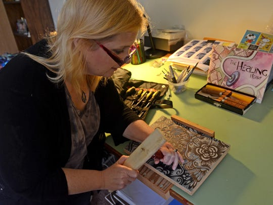 Artist Donna Mitchell-Collins demonstrates the technique she uses to create her artwork Monday, Sept 28, in her studio at her home in Port Huron Township.