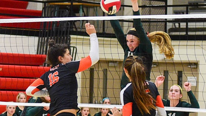 Iowa City West's Emily Halverson (11) goes up to block a volley from West Des Moines Valley's Courtney Twit (16) at the Class 5A-Region 5 regional finals held at Newton High School on Tuesday, Nov. 4, 2014.