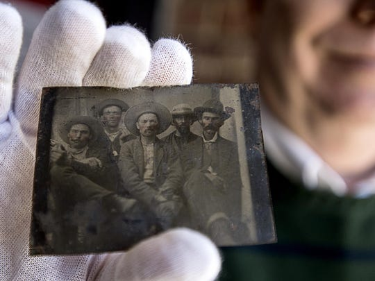 Local lawyer Frank Abrams holds up a tintype picture of five men in hats with cigars and whiskey, one of them believed to be Billy the Kid, Tuesday Jan. 5 in south Asheville. Abrams bought what could possibly be an authentic picture of the notorious Wild West outlaw and sheriff for $10 at Smiley's Flea Market.