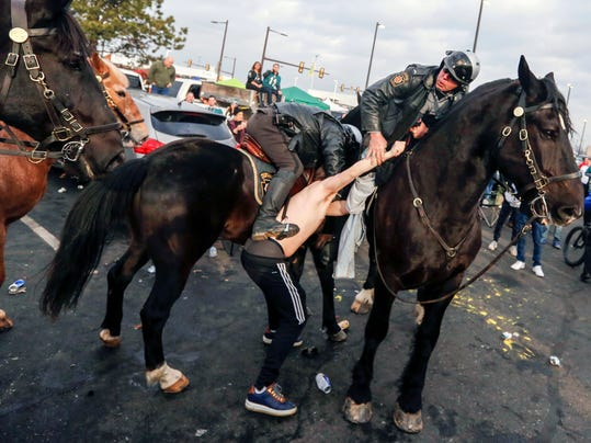 A fan is taken into custody after violence erupted in Parking Lot M as Philadelphia Police and Pennsylvania State Troopers on horseback tried to disperse fans who were tailgating hours before the Philadelphia Eagles were scheduled to host the Minnesota Vikings in the NFC championship NFL football game Sunday, Jan. 21, 2018, in Philadelphia. (Andrew Mills/NJ Advance Media via AP)