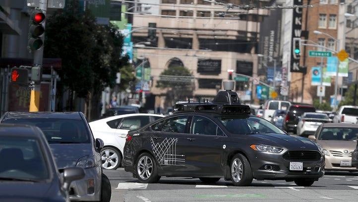 An Uber self-driving car drives down 5th Street on