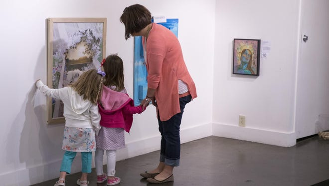 Gwenyth Loudermilk-Ricke (left), 4, with her twin sister Gretchyn Loudermilk-Ricke, take a look at a piece with their mom, Dana Loudermilk of Plainfield, at the Just My Size art show at the Raymond James Stutz Art Gallery in Indianapolis.