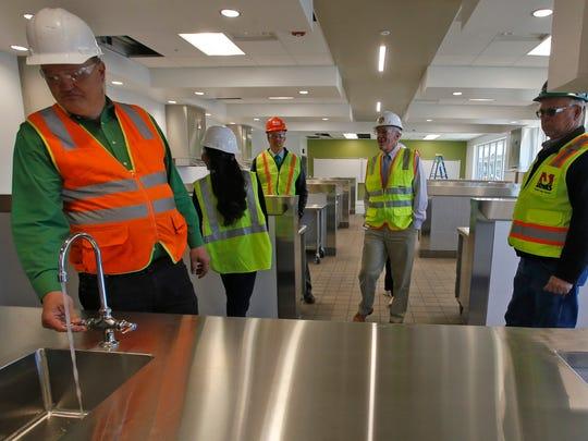 At left, Mike Isaacson, vice president of the Farmington Municipal School District's Board of Education, checks out the faucets in Building A of the new Farmington High School during a tour of the facility on Tuesday. The building was completed as part of the first phase of the project.