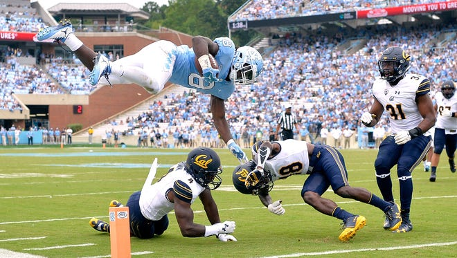 North Carolina running back Michael Carter hurdles Derron Brown #4 and Marloshawn Franklin Jr. #18 of the California Golden Bears and into the end zone for a touchdown during their game at Kenan Stadium on September 2, 2017 in Chapel Hill, North Carolina.