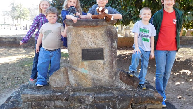 """The children of Joseph Evan Davis Chapter 907 Children of the Confederacy, of Greenville and Bonnie Blue Flag 789 of Anderson, take a pose with history learned at the entrance to Old Stone Church Cemetery Monument """"In Memory of Our Confederate Dead"""" erected by The John C. Calhoun Chapter."""