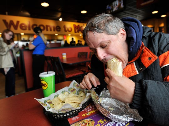 Tanni Stumpf of Spring Grove chomps down on his free burrito after waiting overnight for the opening of Moe's Southwest Grill in Springettsbury Township. In addition to Moe's, Stumpf has waited overnight at Buffalo Wild Wings, Primanti Bros. and 32 times at Chick-fil-a.