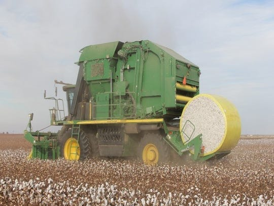 A cotton baler works on a farm in northern Reagan County.