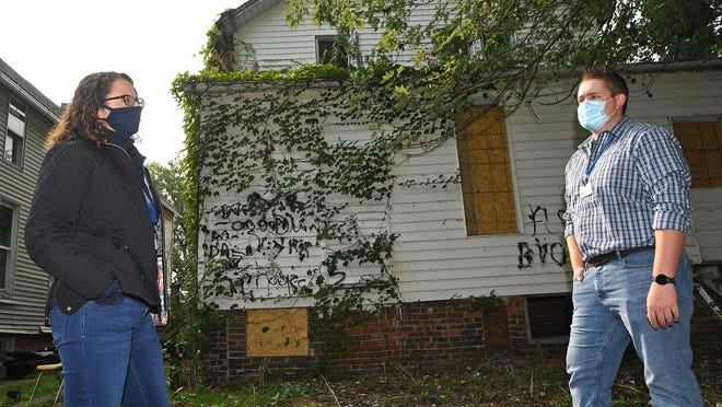 Kathy Wyrosdick, left, and Jake Binney discuss a blighted property in the 900 block of West 11th Street on Sept. 15. Wyrosdick is the director of planning and neighborhood resources for the City of Erie. Binney is one of five code enforcement officers for the city.