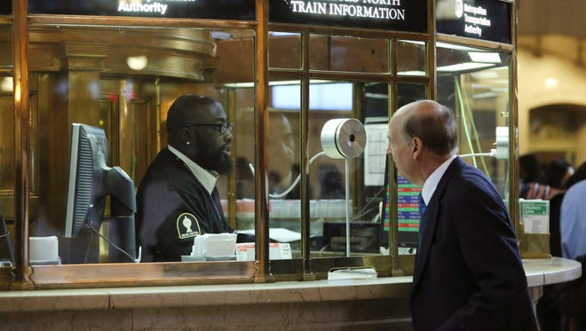 A Metro North costumer service agent helps a morning rush hour commuter with train information at Grand Central Terminal on Sept. 26, 2013, in New York.