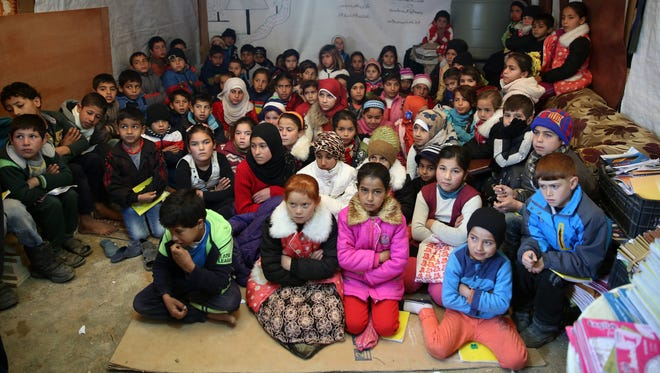 Syrian refugee children sit on the ground as they listen to their teacher inside a tent, a refugee family's home that has been turned into a makeshift school, in a Syrian refugee camp in the eastern town of Kab Elias, Lebanon.