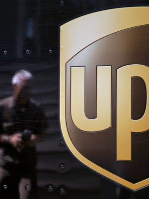 The UPS logo on the side of a company truck with driver Marty Thompson reflected as he returns from a delivery in Cumming, Ga.