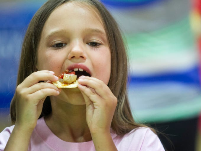 Cathaleen Newman (cq), 8, of Cape Coral tastes some