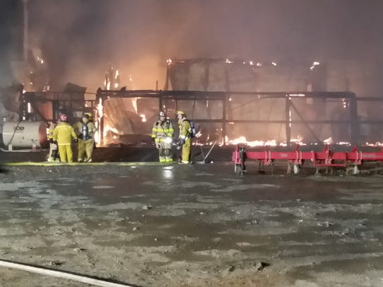 Volunteer firefighters work to extinguish a large barn