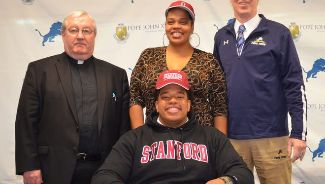 Dalyn Wade-Perry (seated) with (from left) Msgr. Kieran McHugh, Antoinette Wade, Pope John coach Brian Carlson.