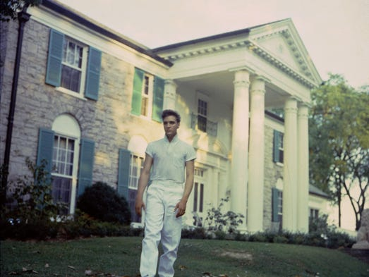 Elvis Presley in front of Graceland in 1957 after purchasing the 13.8 acre estate.