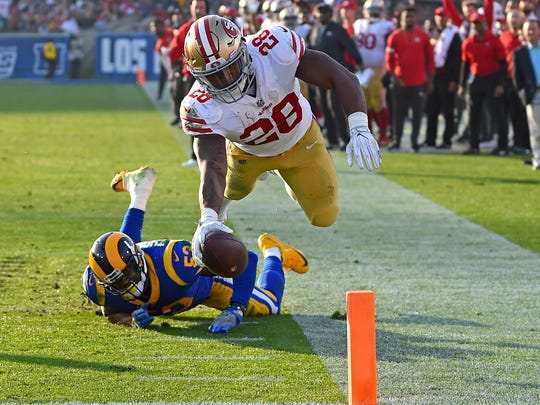 Dec 31, 2017; Los Angeles, CA, USA; San Francisco 49ers running back Carlos Hyde (28) carries the ball past Los Angeles Rams linebacker Carlos Thompson (53) into the end zone for a touchdown in the third quarter of the game at the Los Angeles Memorial Coliseum. Mandatory Credit: Jayne Kamin-Oncea-USA TODAY Sports