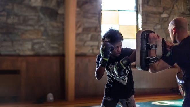 Mixed martial arts fighter Angela Hill focuses and strikes during practice at Summit Church on South French Broad in Asheville. One of few women and the only black woman fighter in the national UFC fighting scene, Hill moved to Asheville with husband Adam Pyrd to train with Triple G Sports Academy and improve her wrestling skills.
