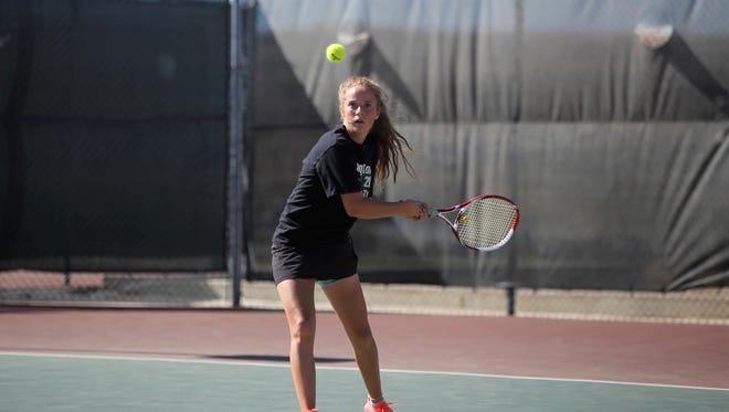 Farmington's Rachel Kelly follows through with a backhand return against Gallup during girls singles Saturday at Farmington Tennis Complex.
