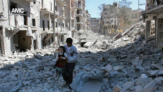 A Syrian man holding a girl in April 2014 as he stands on the rubble of houses that were destroyed by Syrian government forces air strikes in Aleppo, Syria. From the 3-year-old boy who washed ashore on a Turkish beach to the 71 migrants who suffocated in a truck in Austria to the daily scenes of chaos unfolding in European cities as governments try to halt a human tide heading north.