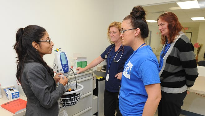 Daphne Chaniz-Rico, health service administrator with Connections Community Support Programs, (left) talks with nurses Heather Battee, Merrisa Williams and Shirley Broome about new procedures at the organization's detox center in Harrington.