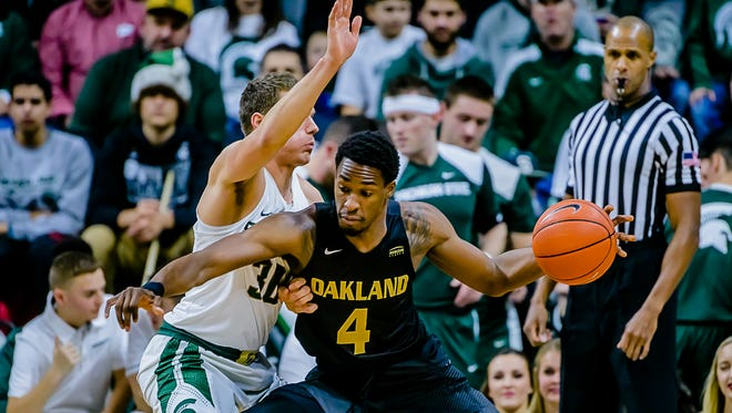Jalen Hayes ,4, of Oakland drives to the basket while being defended by Matt Van Dyk of MSU during their game in December.