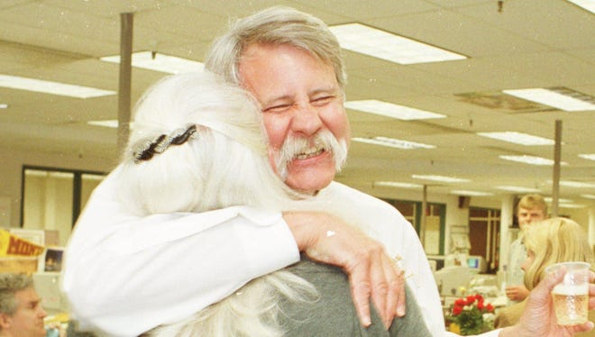 Eric Newhouse, projects editor for the Great Falls Tribune, hugs his wife, Suzie Newhouse, at the Tribune on April 10, 2000, after learning he had won the Pulitzer Prize for explanatory reporting.