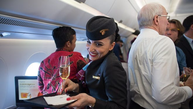 A Qatar Airways' flight attendant makes her way through the crowded aisles during a media preview flight to serve champagne.